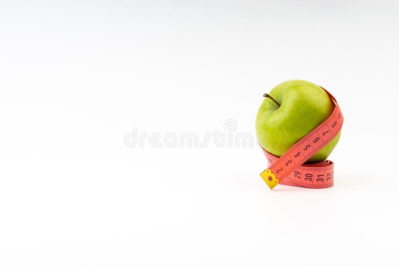 Pomme verte avec la bande de mesure rouge sur le fond blanc images stock