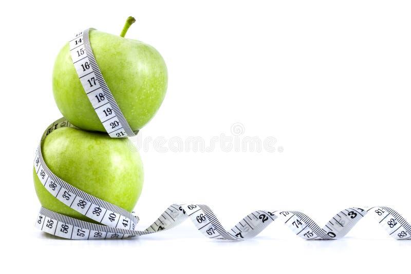 Pomme verte avec la bande de mesure sur le fond blanc dans le concept o image stock