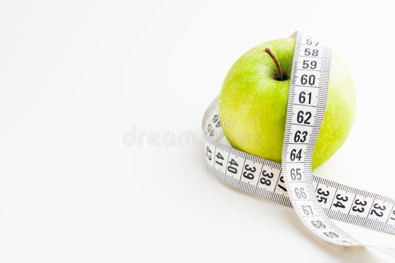 Pomme verte avec le ruban métrique sur le bureau blanc Santé et régime photos libres de droits