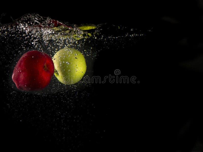 Pomme verte et rouge tombant dans éclabousser l'eau sur l'espace noir de fond et de copie photos libres de droits