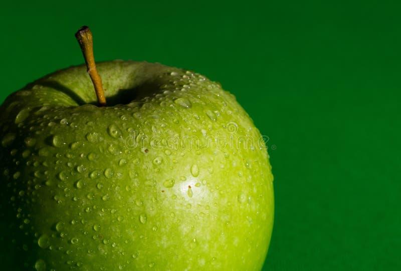 Pomme verte fraîche partiellement vue avec des baisses de l'eau sur le fond vert images libres de droits