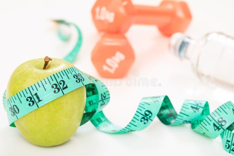 Pomme verte, haltères et bande de mesure photo libre de droits