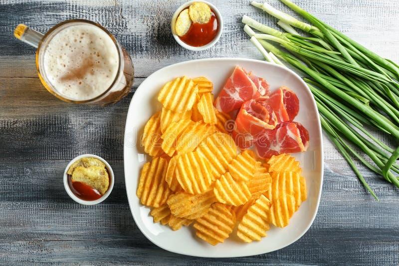 Pommes chips croustillantes avec le lard, les sauces et la bière sur la table en bois photos stock