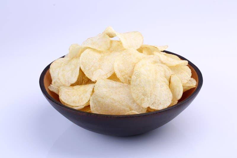 Pommes chips croustillantes dans la cuvette en bois sur le fond blanc images stock