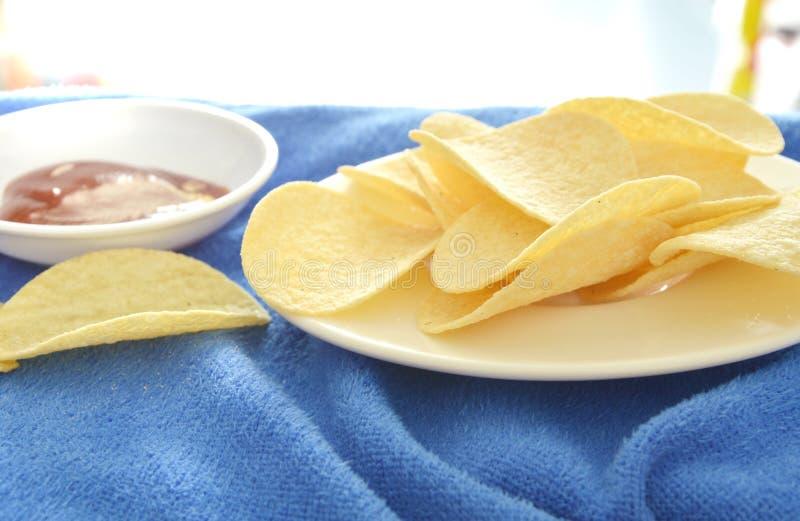 Pommes chips croustillantes et de sel sur le plat plongeant avec la sauce tomate photo stock