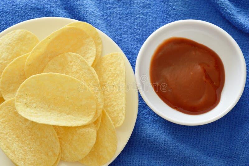 Pommes chips croustillantes et de sel sur le plat plongeant avec le ketchup images stock