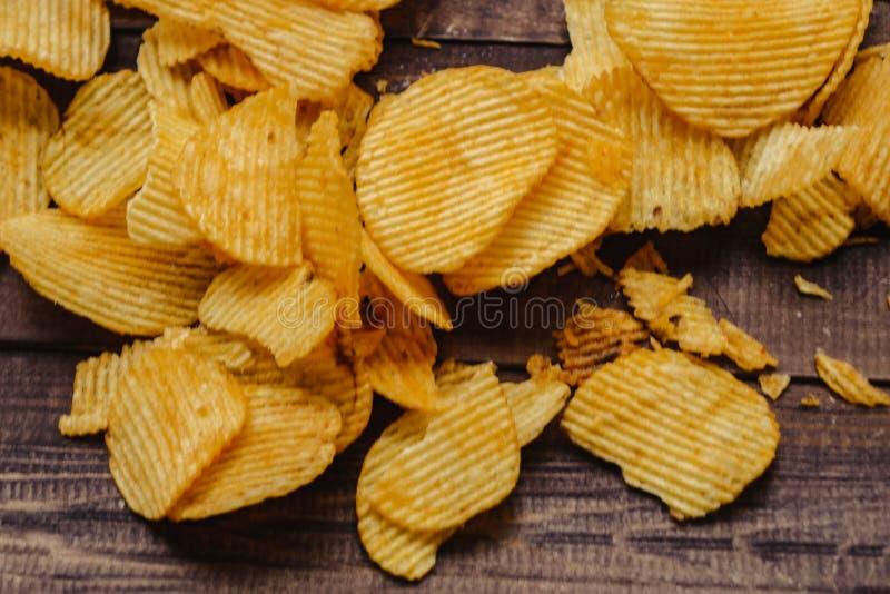Pommes chips croustillantes sur le fond en bois les puces ont commenc? photos stock