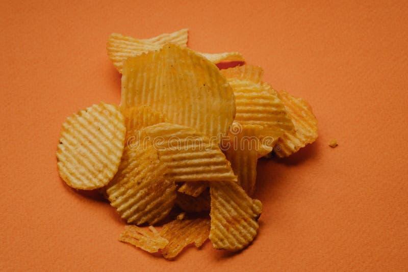 pommes chips croustillantes sur le fond orange Puces de Nachos image stock