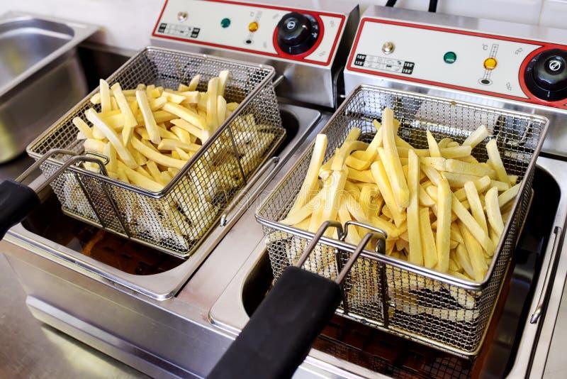 Pommes chips d'or croustillantes s'écoulant sur une friteuse photographie stock