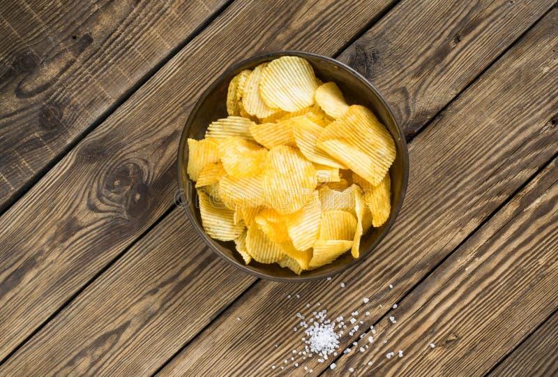 Pommes chips dans la cuvette sur un fond en bois, vue supérieure Chips salés dispersés sur une table photo stock