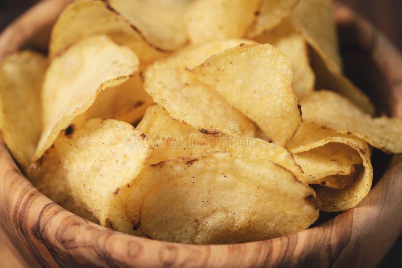 Pommes chips de plan rapproché avec des herbes dans la cuvette en bois sur la table rustique photographie stock libre de droits