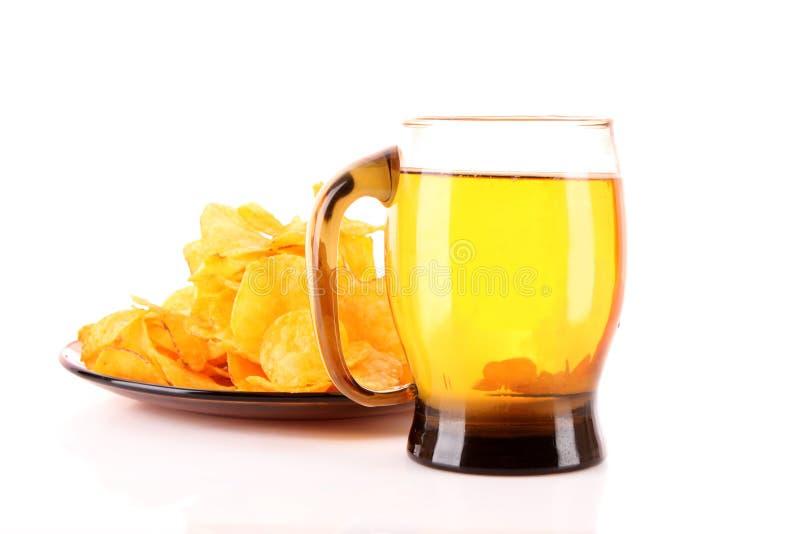 Pommes chips dedans la plaque avec de la bière image stock