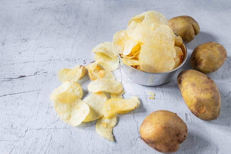 Pommes chips et pomme de terre crue frites dans une cuvette image stock