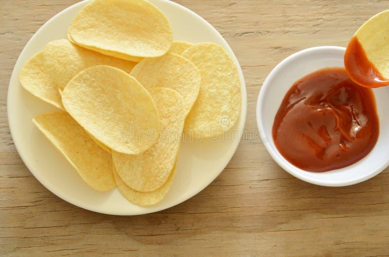 Pommes chips plongeant avec le ketchup sur la tasse photographie stock