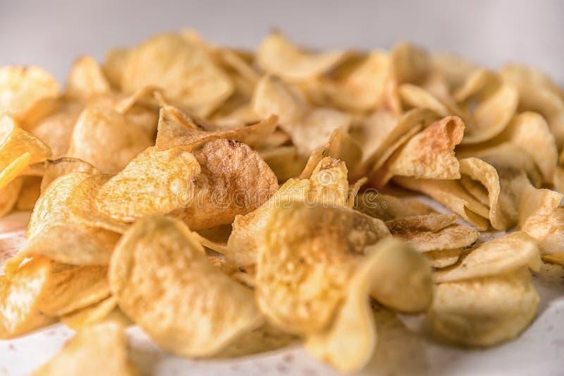 Pommes chips rôties d'un plat sur un fond blanc images stock