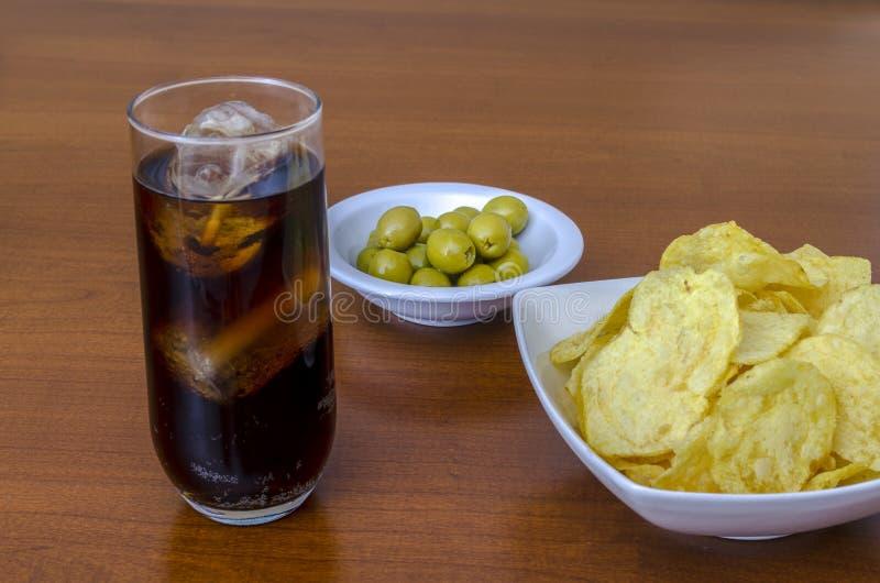 Pommes chips salées dans la cuvette avec le kola et les olives image stock