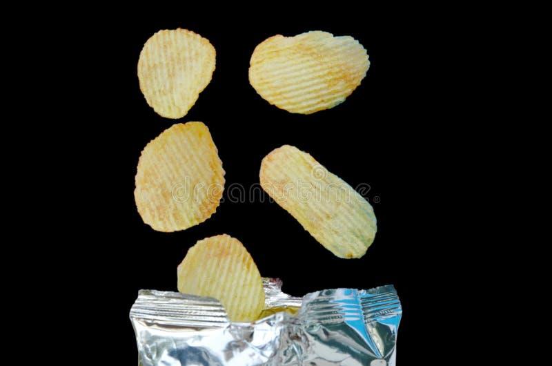 Pommes chips tombant à l'emballage de papier aluminium sur le fond noir photographie stock