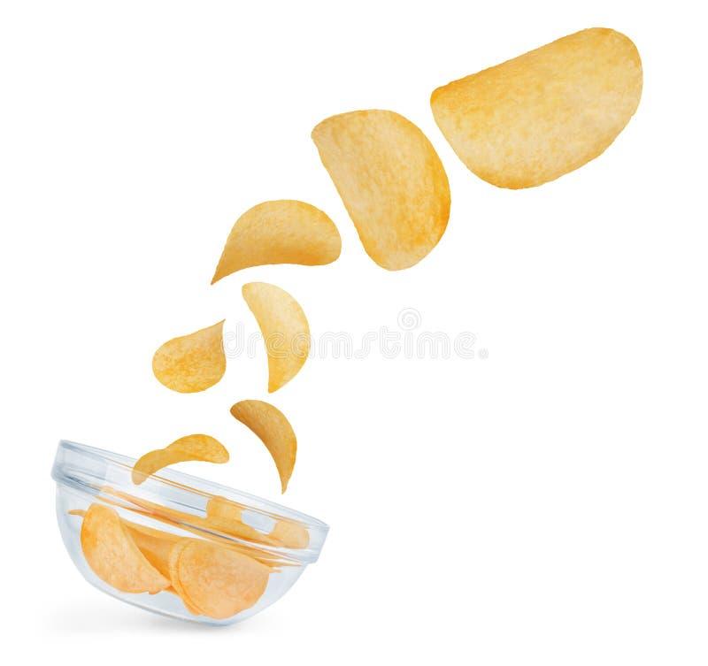Pommes chips tombant dans une cuvette d'isolement sur le blanc photos stock