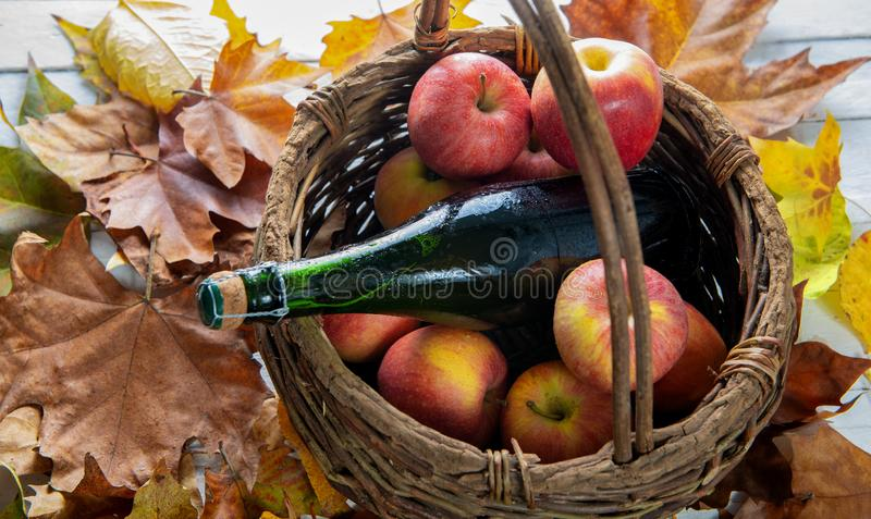 Pommes dans le panier et la bouteille de cidre de la Normandie photo stock