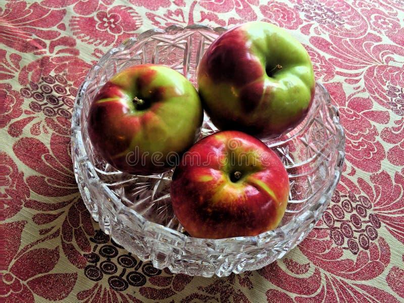 Pommes dans un plat avec le fond floral de nappe photographie stock