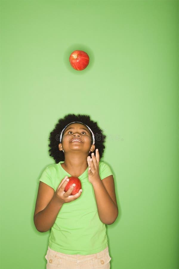 Pommes de jonglerie de fille. photographie stock libre de droits