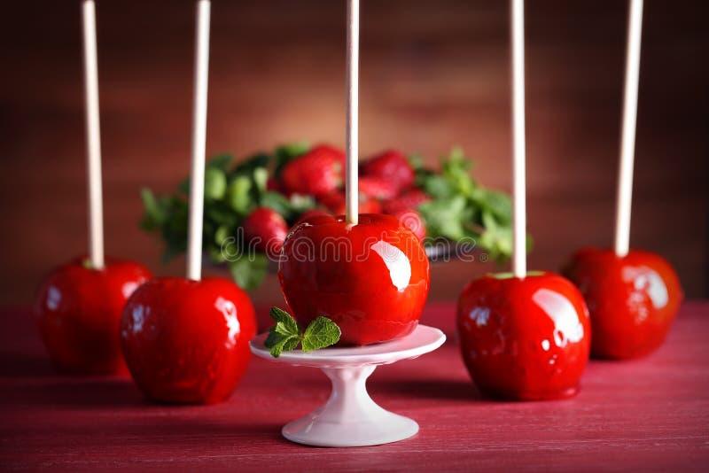 Pommes de sucrerie sur la table rouge image stock