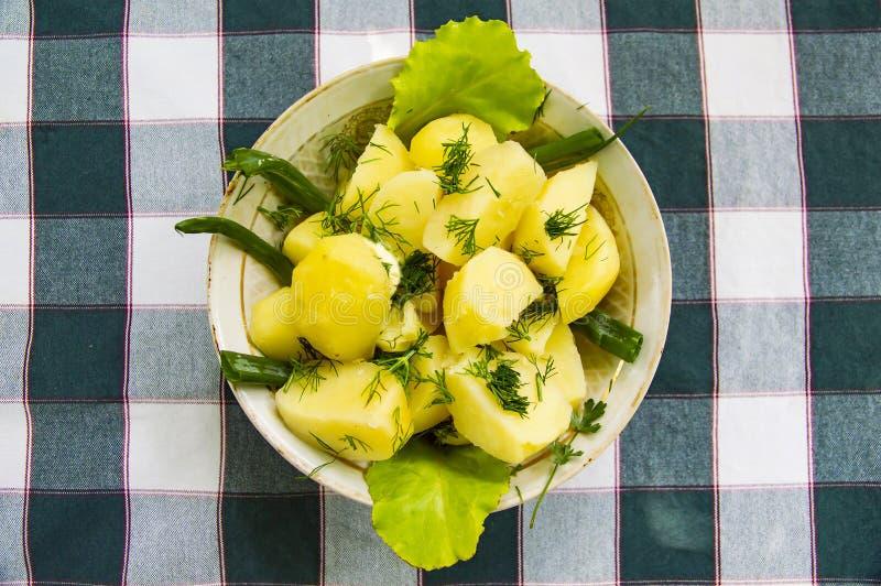 Pommes de terre avec des herbes dans un plat sur une nappe dans une cage photos stock