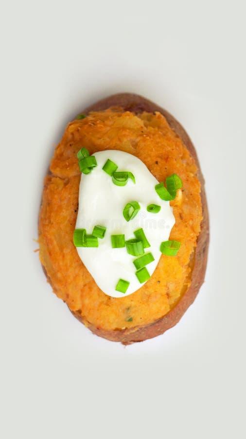 Pommes de terre bourrées décorées à l'oignon de ressort d'un plat blanc sur un fond blanc Vue supérieure photo libre de droits