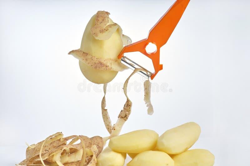 Pommes de terre crues épluchées, épluchant des pommes de terre et une éplucheuse sur un plan rapproché blanc de fond images stock