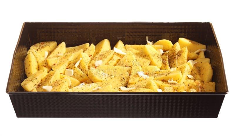 Pommes de terre crues avec des épices prêtes à être rôti images stock