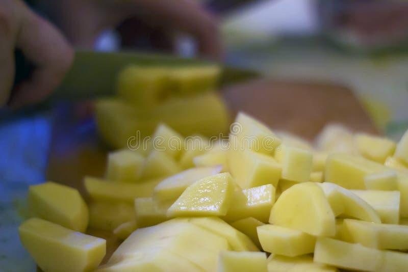 Pommes de terre crues coupées en tranches et épluchées sur un conseil procédé de préparation de pomme de terre photos libres de droits