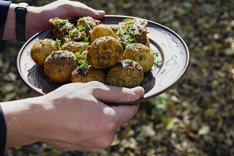 Pommes de terre cuites au four avec des nervures de porc sur le feu présenté d'un plat d'argile, décoré des verts D?ner en nature image stock