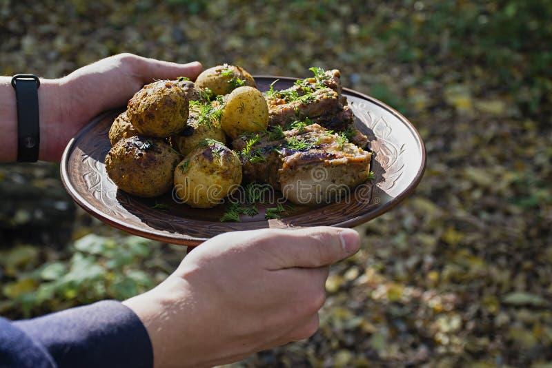 Pommes de terre cuites au four avec des nervures de porc sur le feu pr?sent? d'un plat d'argile, d?cor? des verts D?ner en nature images libres de droits