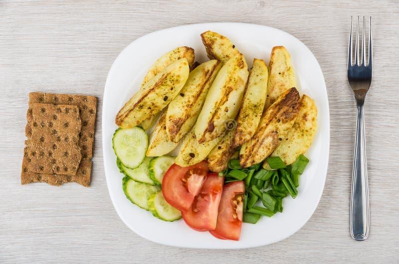 Pommes de terre cuites au four avec des tomates, des concombres et le pain croustillant sur la table photographie stock libre de droits