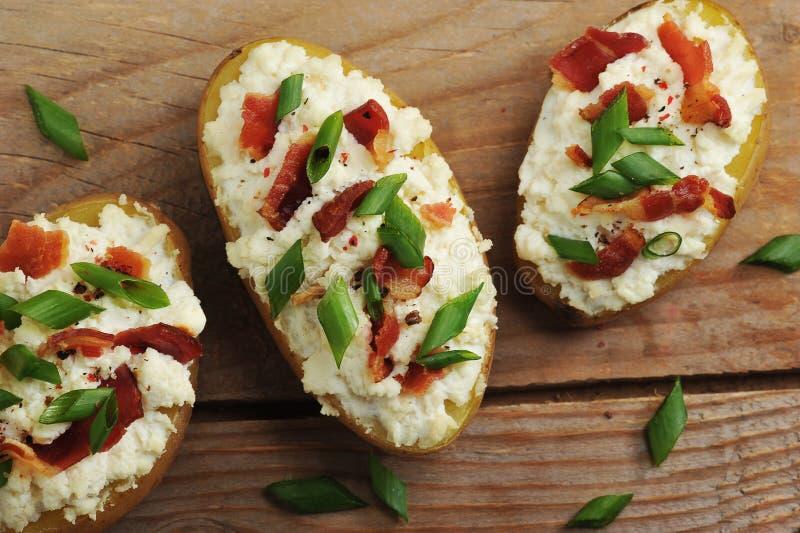 Pommes de terre cuites au four bourrées dans la veste avec le lard et le fromage photos stock