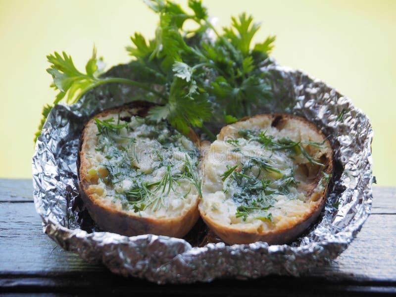 Pommes de terre cuites au four dans les charbons avec les herbes et le beurre photo stock