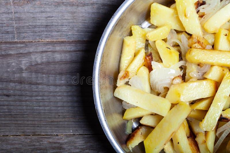 Pommes de terre délicieuses de rôti à l'oignon et aux épices dans une casserole sur la serviette de cuisine sur la vieille table  image stock