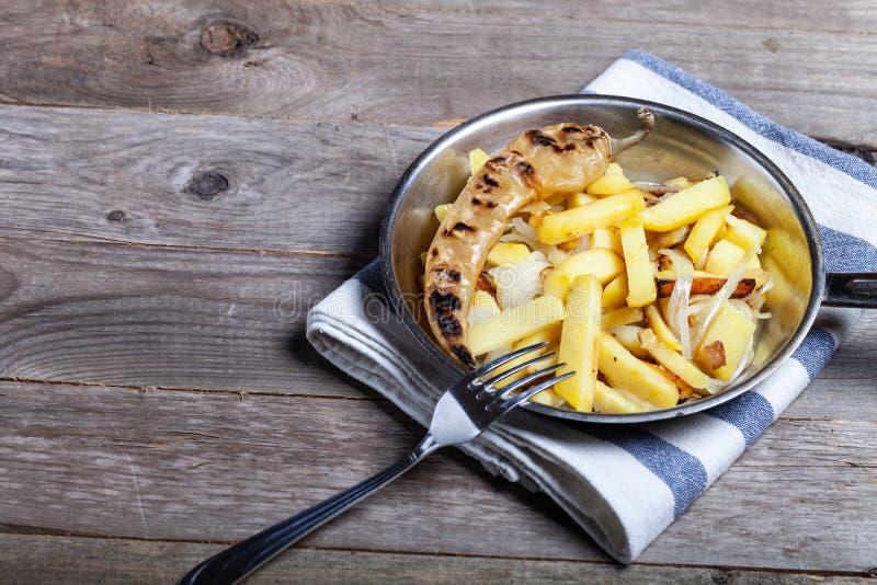 Pommes de terre délicieuses de rôti à l'oignon et aux épices dans une casserole sur la serviette de cuisine sur la vieille table  photos libres de droits