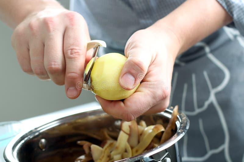 Pommes de terre d'épluchage d'homme Fonctionnement de cuisine Préparez la nourriture photographie stock