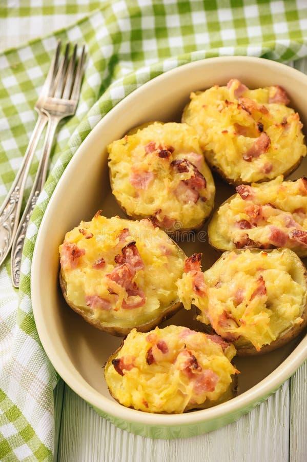 Pommes de terre en robe de chambre de jambon et de fromage sur le fond foncé image stock