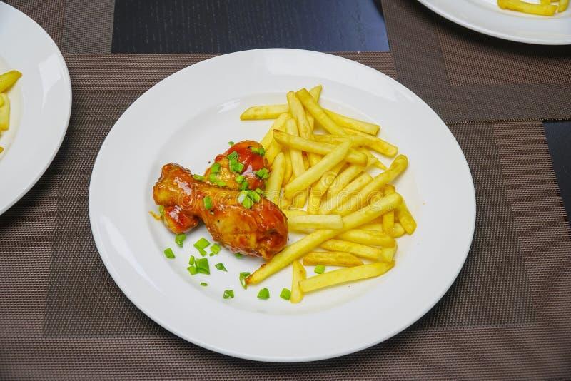 Pommes de terre frites avec des jambes de poulet et des oignons verts coupés de plat photos stock