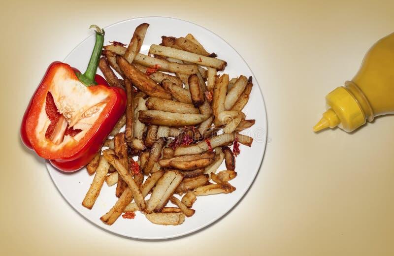 Pommes de terre frites faites maison d'un plat, poivre, sauce à moutarde photos libres de droits