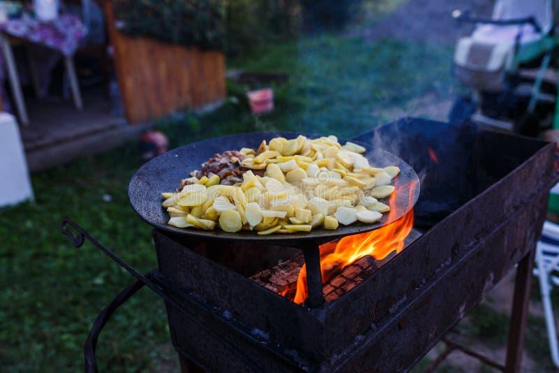 Pommes de terre de friture sur le feu ouvert en plein air photo stock