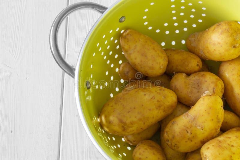 Pommes de terre, lavées, dans une passoire vert clair en métal image libre de droits