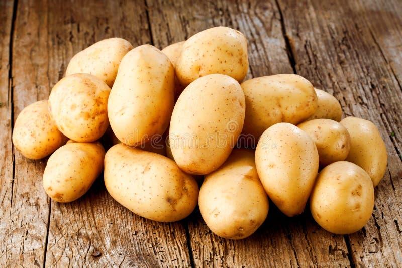 Pommes de terre organiques crues fraîches sur le vieux fond de vintage photographie stock