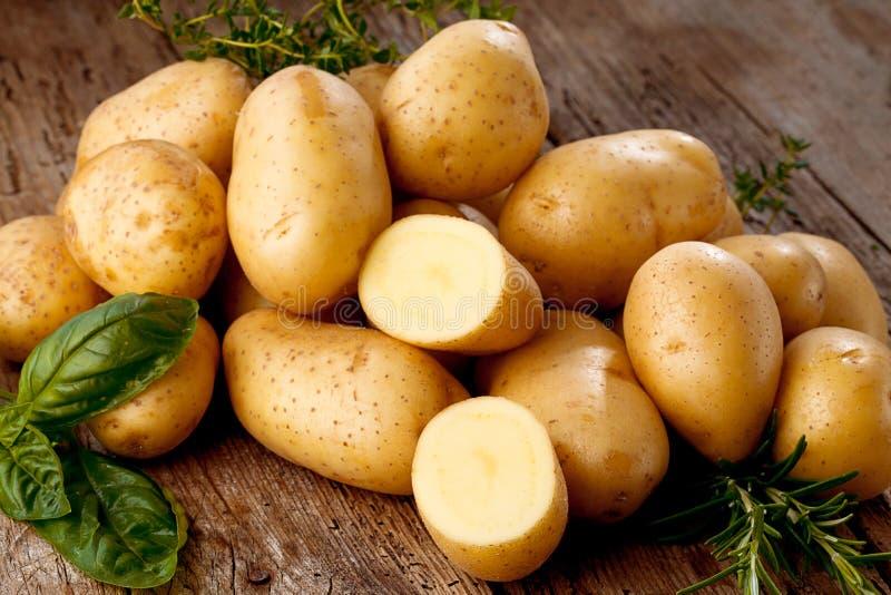 Pommes de terre organiques crues fraîches sur le vieux fond de vintage image stock