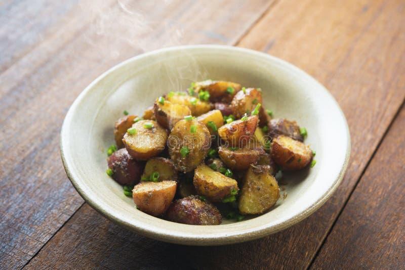 Pommes de terre rôties par four sur la table en bois images libres de droits