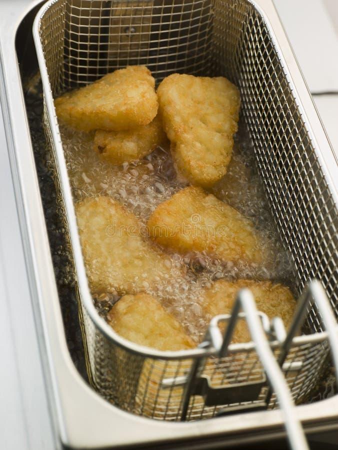 Pommes de terre rissolées étant cuites à la friteuse en huile de maïs photos stock