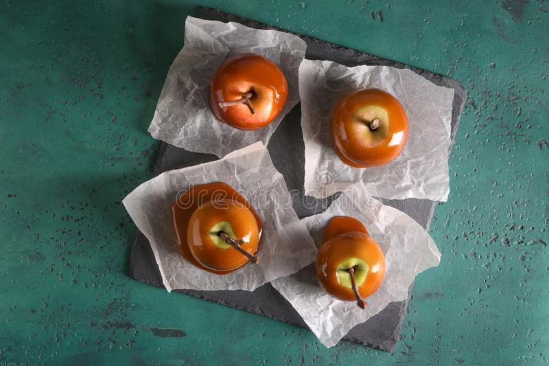 Pommes Delicious de caramel avec des branches d'arbre de plat d'ardoise photo libre de droits