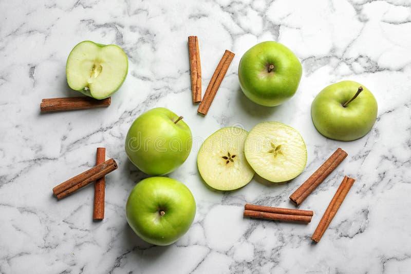 Pommes et bâtons de cannelle frais sur la table de marbre photos libres de droits